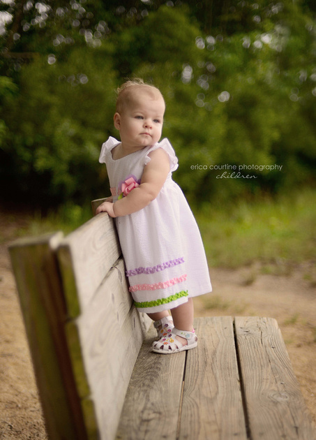 A little girl stands on a bench at Lake Benson in Garner, NC during her first birthday photography session.