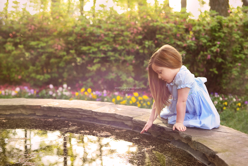 Little girl sits by a fountain at WRAL Azalea Garden during a child portrait session in Raleigh NC.