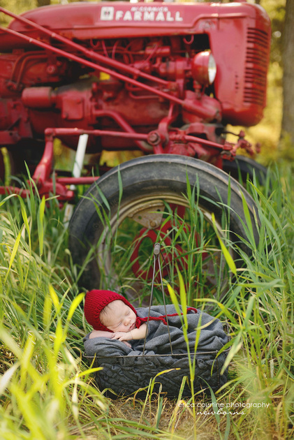 a newborn baby boy sleeps in front of his antique red farmall tractor during his outdoor newborn photography session in raleigh nc.