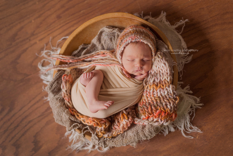 A baby girl curled up in a wooden bowl during her in-home newborn photography session near Raleigh NC.