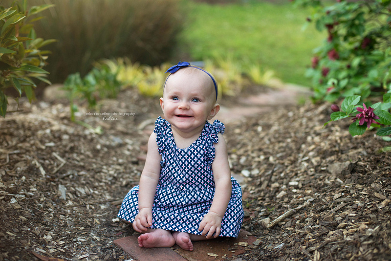 A baby girl smiles for a picture during her 6 month old photo session with Erica Courtine Photography.