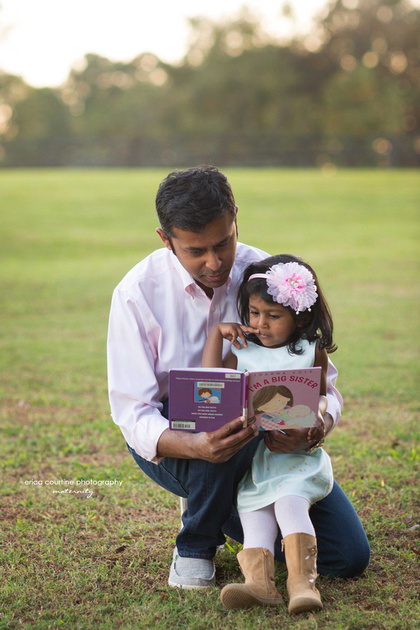 A daddy and little girl read a book during a maternity photography shoot with Erica Courtine Photography in Holly Springs, NC.