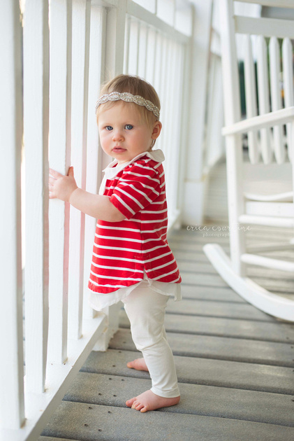 A baby girl walks around the decks at Bass Lake Park in Holly Springs, NC, during her photography session.