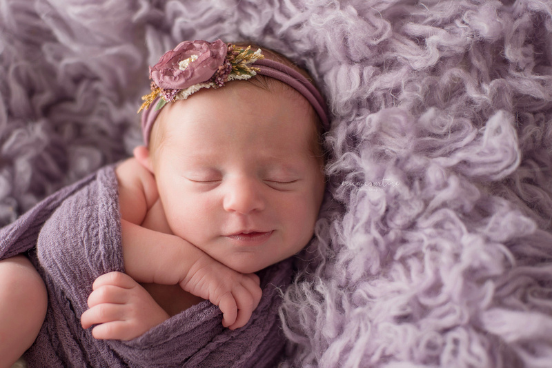 Raleigh Cary Apex Holly Springs Affordable Newborn Baby Photographer - A baby girl on a lavender fur smiling during a photo shoot