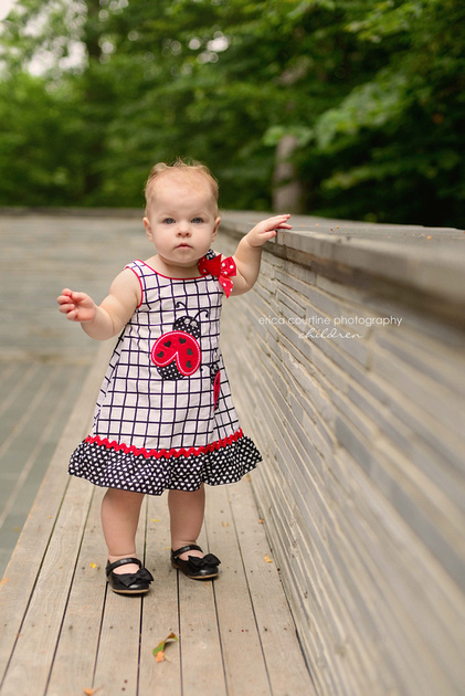 A little girl stands by a beautiful stone wall at White Deer Park in Garner, near Raleigh, NC during her first birthday photography session.
