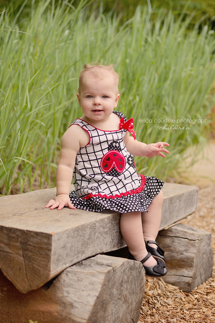 A little girl sits on a bench at White Deer Park near Raleigh, NC during her first birthday photography session.