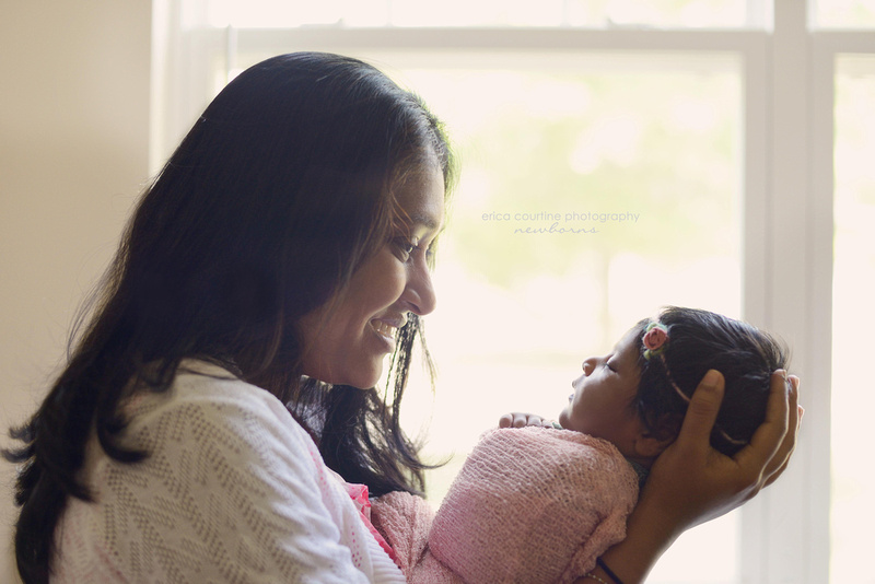 A  new mother holds her newborn daughter during a newborn photo session in Durham, NC.