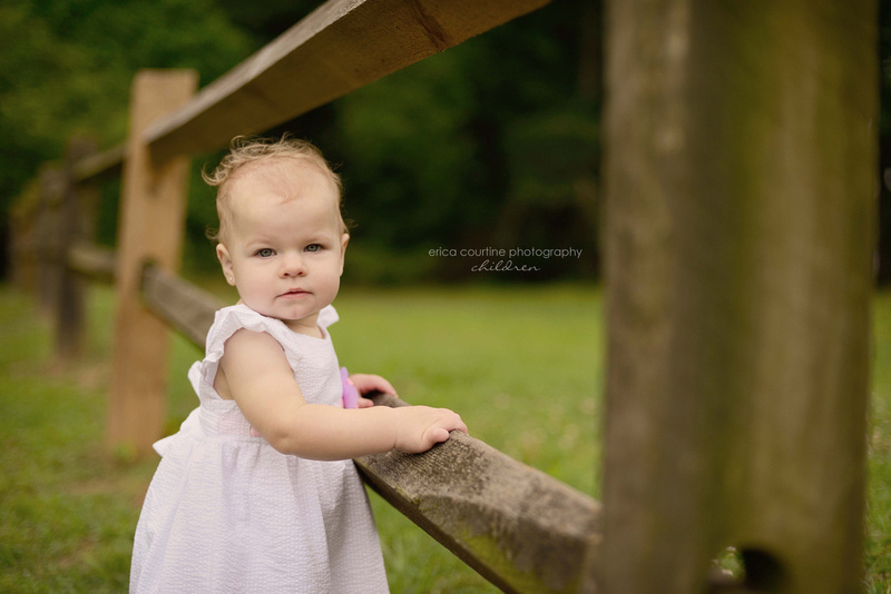 A baby girl stands by a farm fence in Garner, NC at Lake Benson Park during her first birthday photography session.