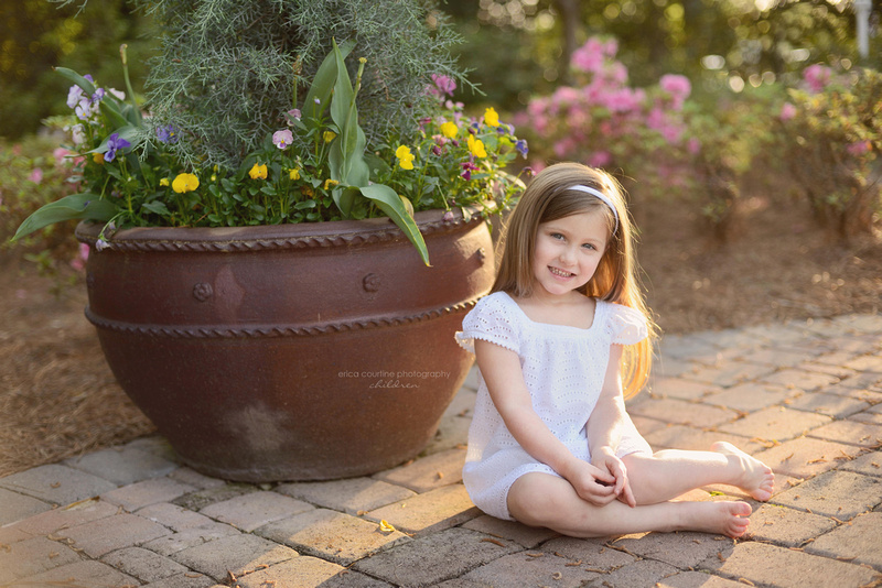 A little girl sits during a photography session at WRAL Azalea Garden in Raleigh NC.  Raleigh Cary Holly Springs Family Photographer