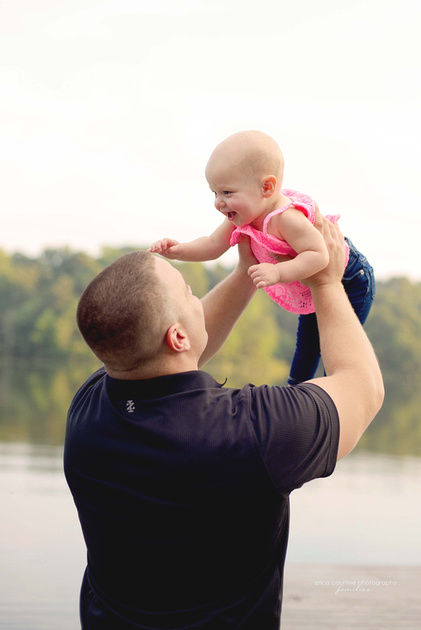 A baby girl poses with daddy during a family photography session by Raleigh family photographer Erica Courtine.