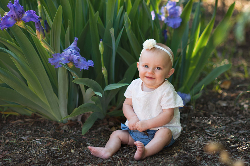 A baby girl sits among purple irises at raulston arboretum in raleigh nc during her 6 month photography session.