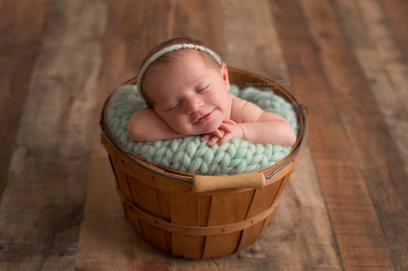Smiling baby girl during a newborn photography session in Fuquay Varina outside of Raleigh NC.