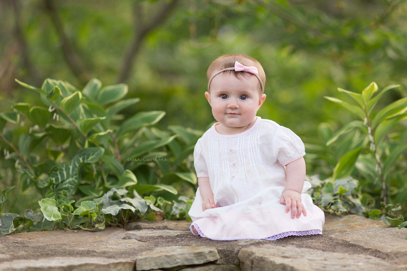 Raleigh NC Family Photographer - a baby sitting among flowers during a photo session at Raulston Arboretum.