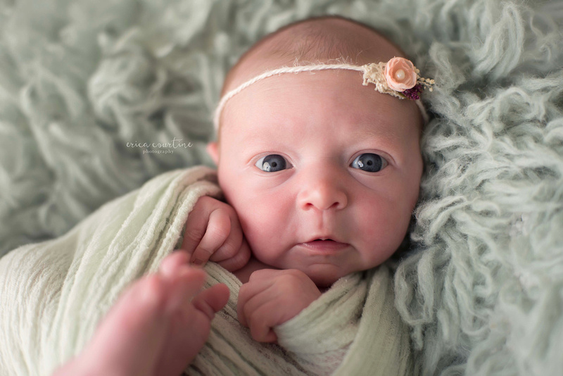 A wide eyed alert newborn baby girl during a photo session in Fuquay Varina, outside of Raleigh, NC.