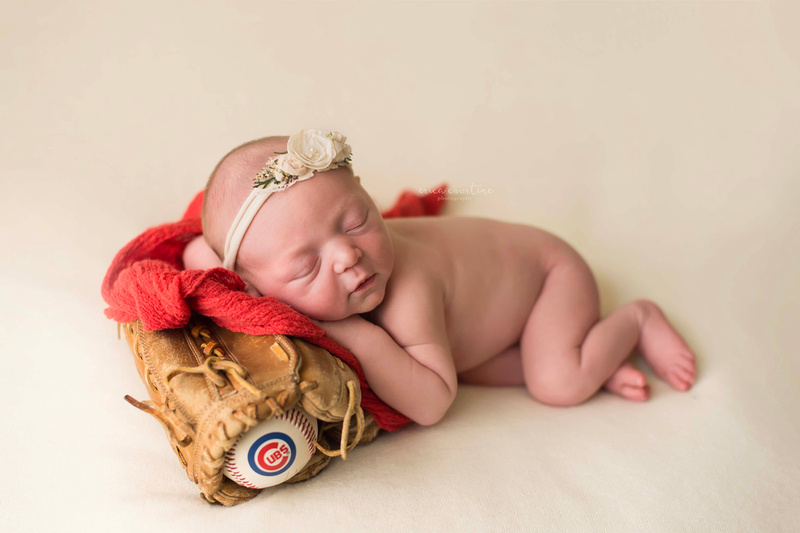 A newborn baby girl poses with chicago cubs baseball themed props during a newborn photography session in Raleigh, NC.