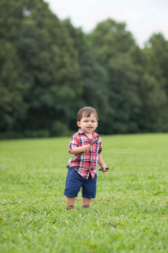 A little boy in a big open field during a photography session raleigh cary apex holly springs fuquay varina nc