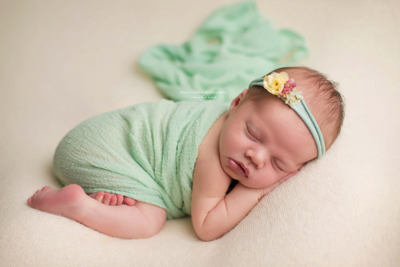 A newborn baby girl wrapped in green fabric during her newborn photo shoot outside of Apex, NC.