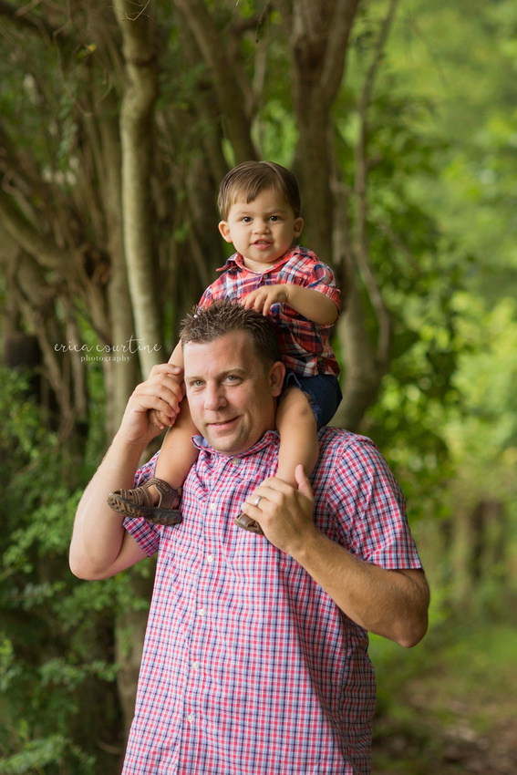 A little boy on his daddy's shoulders during a family photography session at Sugg Farm in Holly Springs, near Raleigh, NC.