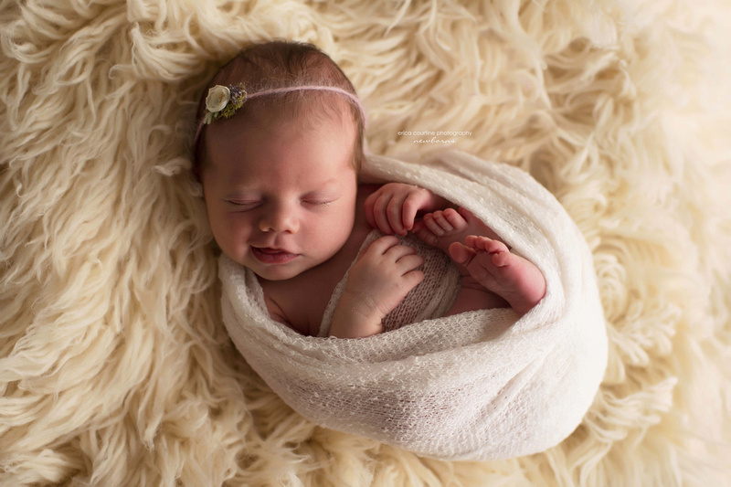 A newborn baby girl smiles during a photography session in her home in Apex, outside of Raleigh, NC.