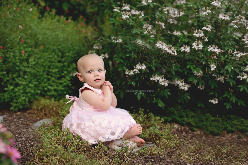 A little girl sits in a garden at Bass Lake Park in Holly Springs, North Carolina, during a children's photography session.