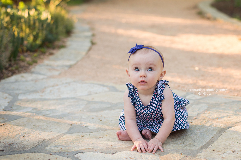 A baby girl sits on a path at raulston arboretum in raleigh nc for her 6 month milestone photography session.