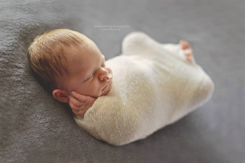newborn baby boy on gray by newborn photographer serving raleigh cary apex holly springs fuquay varina nc.