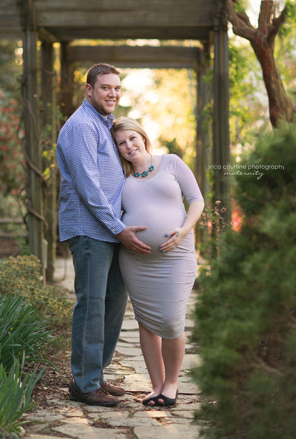 A couple poses for a pregnancy photo shoot under an arbor at raulston arboretum in raleigh nc