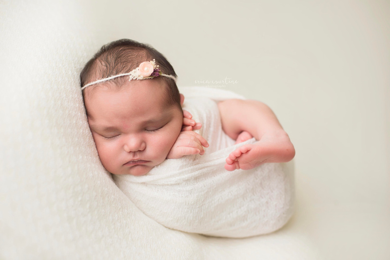 A baby girl on white during a natural, organic, beautiful newborn portrait session with digital packages, by award winning photographer.