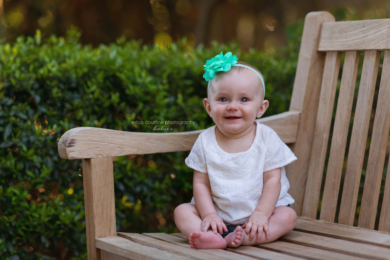 A baby girl sits on a bench at jc raulston arboretum in raleigh nc during her 6 month photography session with Erica Courtine Photography.
