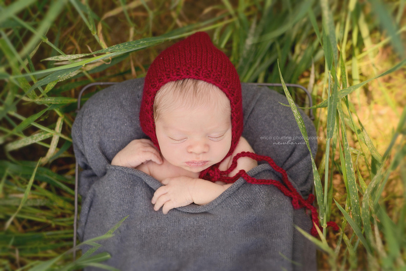 A newborn baby boy with a red knit hat during a newborn portrait session  raleigh cary holly springs apex newborn photographer